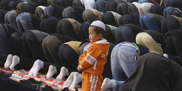 Boy watches as Muslims attend prayer session at mosque during Eid al-Fitr in Lanzhou
