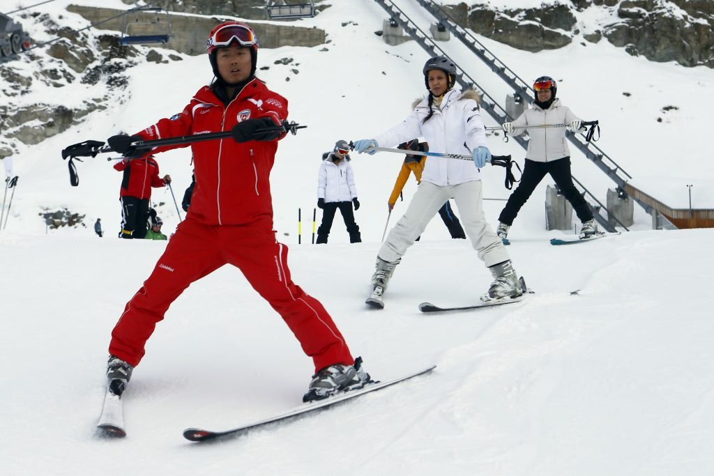 Chinese ski instructor Li exercises with clients during a private beginner ski course in the alpine resort of Zermatt