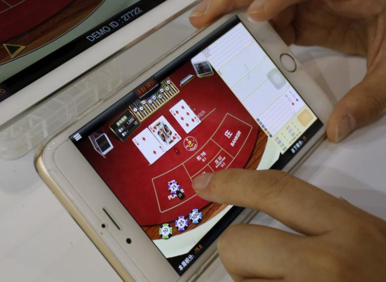 An attendant demonstrates an online baccarat game on a smartphone at the Global Gaming Expo (G2E) Asia in Macau, China May 19, 2015. REUTERS/Bobby Yip/Files